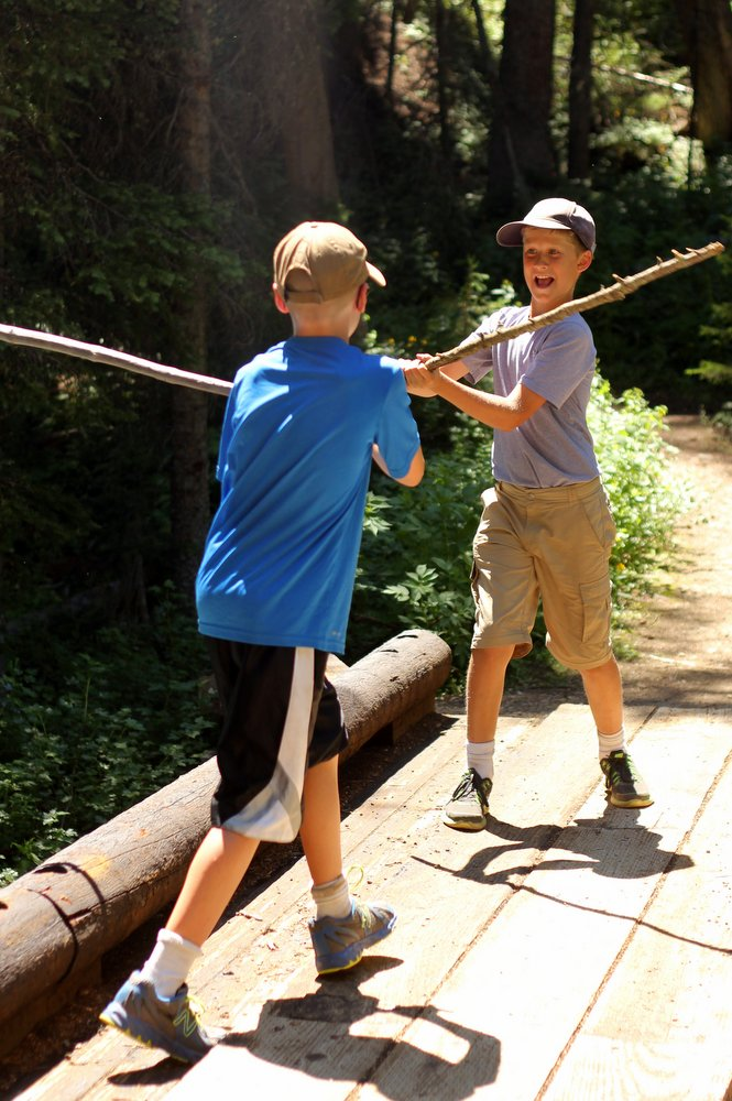 Bode and Heron Duel on a bridge over a creek on the East Rosebud Trail