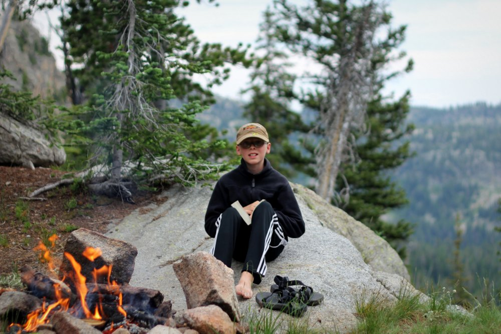 Bode warms up near the fire, Bald Knob Lake, East Rosebud Trail